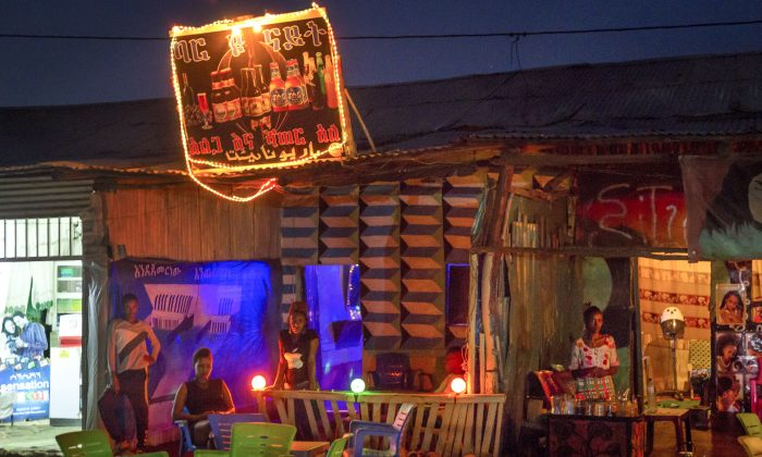 In this photo taken Thursday, June 4, 2015, female migrants work at a bar at night in Metema, in northwestern Ethiopia next to the border with Sudan. The town is a center for a booming trade in migrants from Ethiopia, Eritrea, Somalia and Sudan, with many hoping to make their way to Europe, but life here is now a cat-and-mouse game: The authorities are cracking down, yet the migrants just keep coming, often risking death. (AP Photo/Mulugeta Ayene)