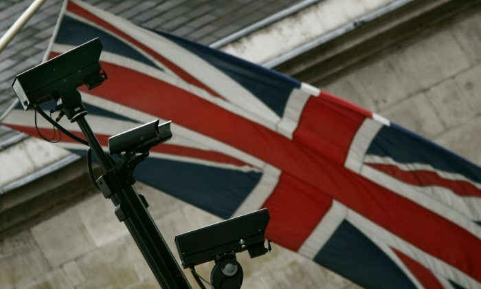 FILE - In this July 26 2005 file photo, a closed-circuit surveillance cameras, with a Union flag at rear, keeps watch in central London. (AP Photo/Lefteris Pitarakis)