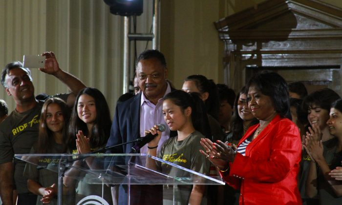 Ride2Freedom leader Annie Chen (Center) addresses the audience at Rainbow/Push headquarters while the Rev. Jesse Jackson (Left) and Rep May Flowers look on. (Chris Jasurek/Epoch Times)
