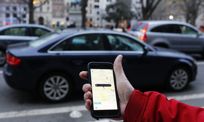 An UBER application is shown as cars drive by in Washington, DC on March 25, 2015. (Andrew Caballero-Reynolds/AFP/Getty Images)