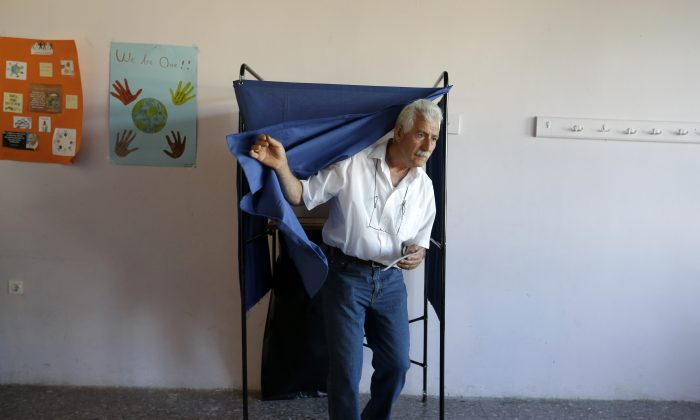 A man casts his vote at polling station in Athens, Sunday, July 5, 2015. (AP Photo/Thanassis Stavrakis)