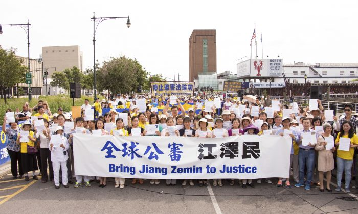 Falun Gong practitioners hold their criminal complaints at a rally in front of the Chinese consulate in New York City on July 3, 2015, to support the global effort to sue Jiang Zemin. (Larry Dye/Epoch Times)