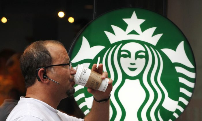 FILE - In this July 11, 2013  file photo, a man drinks a Starbucks coffee in New York. Starbucks says it's hiking prices again starting Tuesday, July 7, 2015, with the increases ranging from 5 to 20 cents for most affected drinks. (AP Photo/Mark Lennihan, File)