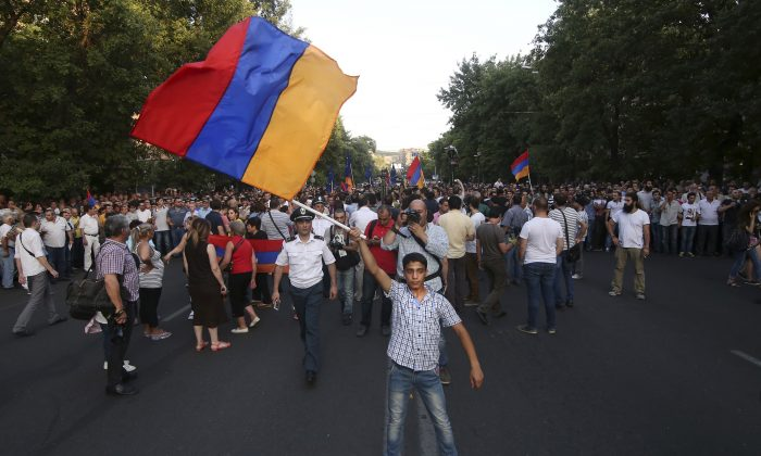 In this photo taken late Monday, June  22, 2015, an Armenian protester waves a national flag during a protest rally in the Armenian capital of Yerevan against a hike in electricity prices. (Hrant Khachatryan/PAN Photo via AP)