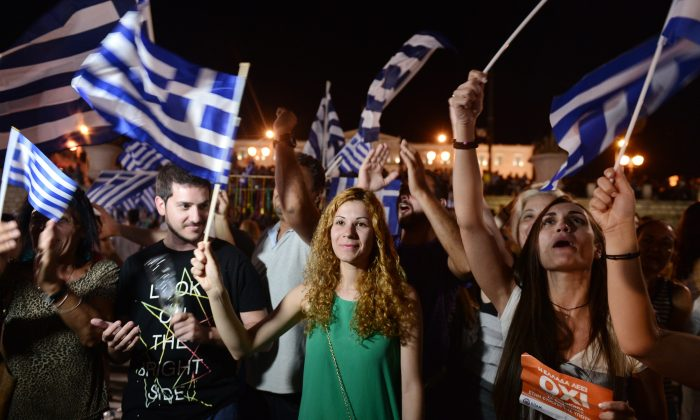 People celebrate in Athens on July 5, 2015 after the first exit-polls of the Greek referendum. Over 60 percent of Greeks rejected further austerity dictated by the country's EU-IMF creditors in a referendum, results from 20 percent of polling stations showed. (LOUISA GOULIAMAKI/AFP/Getty Images)