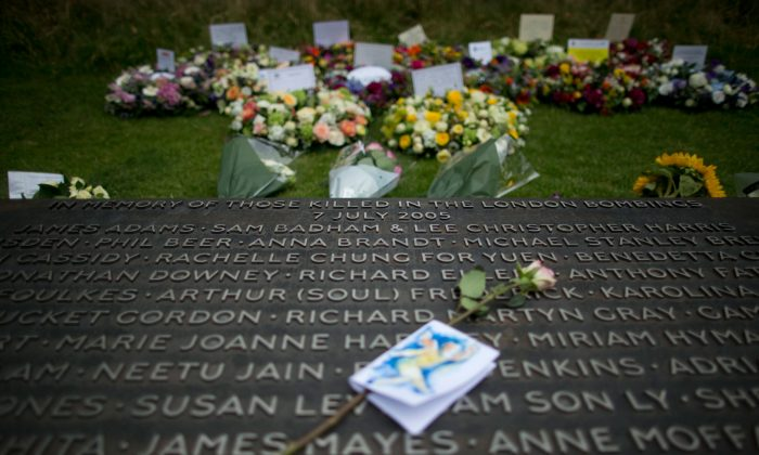 Floral wreaths lie beside a plaque bearing the names of victims at the 7/7 memorial, on the 10th anniversary of the attacks, in Hyde Park, London, on July 7, 2015. (AP Photo/Matt Dunham)