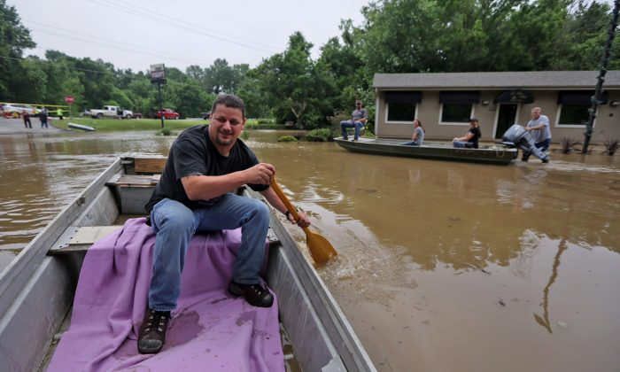 A man uses a boat to look around Lakeside Manor mobile home park after flash flooding took over the area on July 2, 2015. (Huy Mach/St. Louis Post-Dispatch via AP)