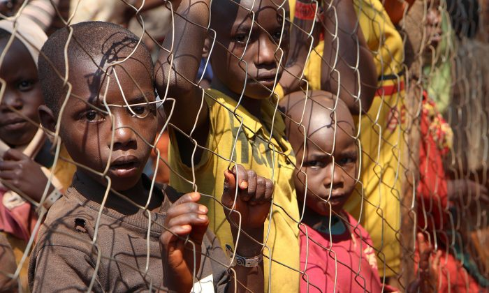 Burundian children, who fled their country, stand behind a fence as they wait to be registered as refugees at Nyarugusu Camp, in northwestern Tanzania, on June 11, 2015. (Stephanie Aglietti/AFP/Getty Images)