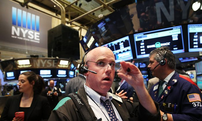 """Traders wait for trading to resume on the floor of the New York Stock Exchange (NYSE) after trading was halted due to a """"technical glitch"""" on July 8 in New York City. A cybersecurity firm is warning hackers may be probing the NYSE networks for a larger attack. (Spencer Platt/Getty Images)"""