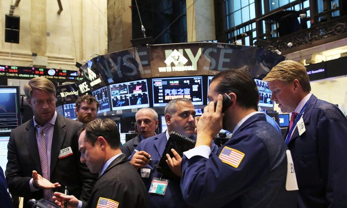 Traders work on the floor of the New York Stock Exchange (NYSE) after trading was paused for nearly four hours on July 8 in New York City. A prominent member of the hacker collective Anonymous says the Chinese regime is likely behind the outage. (Spencer Platt/Getty Images)