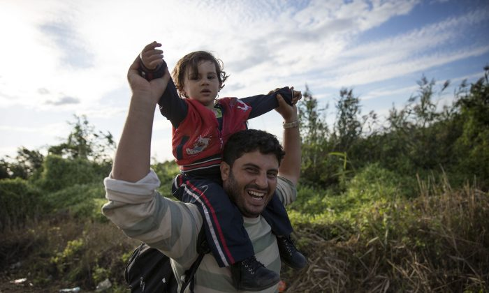 Migrants cross into Hungary as they walk over railroad tracks at the Serbian border with Hungary in Horgas, Serbia, on Sept. 7, 2015. (Dan Kitwood/Getty Images)