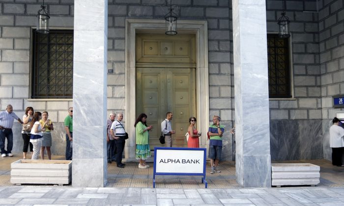 People stand in a queue to use the ATMs of a bank in Athens, Greece, Wednesday, July 8, 2015. (AP Photo/Petr David Josek)