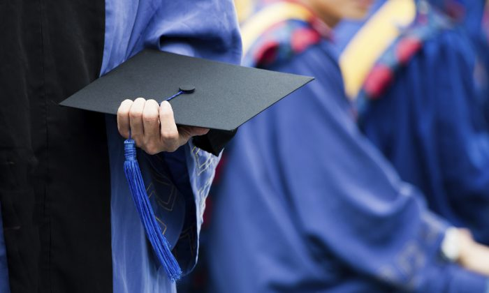 Stock image of a college student at a graduation ceremony. (Hxdbzxy/iStock)