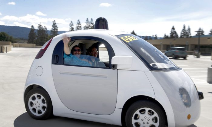 In this May 13, 2015 photo, Teresa Favuzzi, of Sacramento, waves as she gets a ride in the new Google self-driving prototype car during a demonstration at Google's campus in Mountain View, Calif. The plan of traditional automakers is to gradually automate more functions of driving until, perhaps by 2025, some cars will be fully capable of driving themselves. But Google, Alibaba, Baidu and other tech companies are aggressively working on their own self-driving vehicles, and could leapfrog the car industry in bringing them to market. (AP Photo/Tony Avelar)