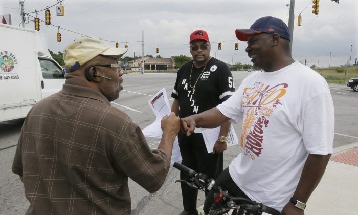 In this photo taken June 15, 2015, Chris Samuel, left, gets a fist bump from supporter Milton Stanciel after talking about rising crime in Detroit.  (AP Photo/Carlos Osorio)