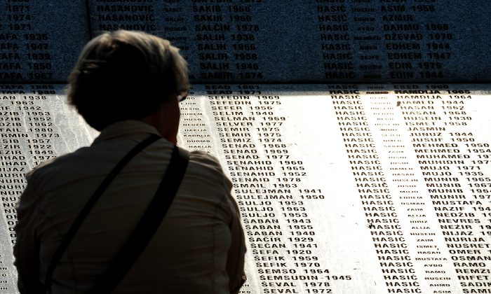A visitor stands in front of the memorial wall at the Potocari Memorial cemetery near the Eastern-Bosnian town of Srebrenica, on July 4, 2013. (Elvis Barukcic/AFP/Getty Images)