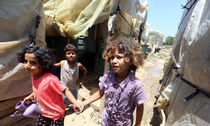 Syrian refugee children walk at an informal refugee camp in the area of Zahrani, south of the Lebanese capital Beirut, on July 9, 2015. (Joseph Eid/AFP/Getty Images)