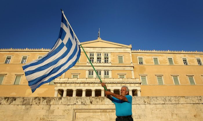 Athenians wave flags as they converge on Syntagma Square to show their support for the euro on July 9, 2015 in Athens, Greece. (Christopher Furlong/Getty Images)
