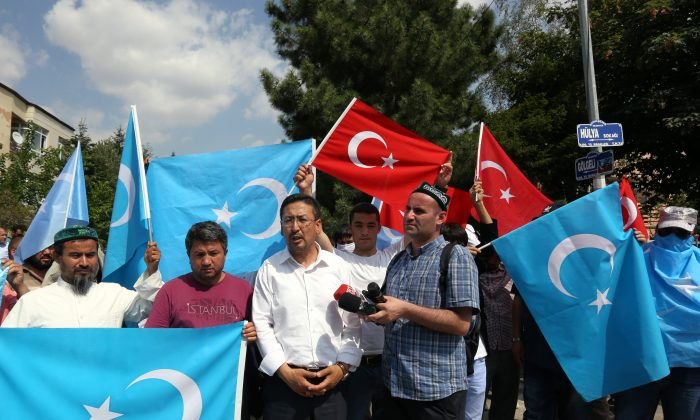 Uighurs demonstrate before the riot police used pepper spray to push back a group of Uighur protesters who tried to break through a barricade outside the Chinese Embassy in Ankara, Turkey, Thursday, June 9. 2015.   (AP Photo/Burhan Ozbilici)