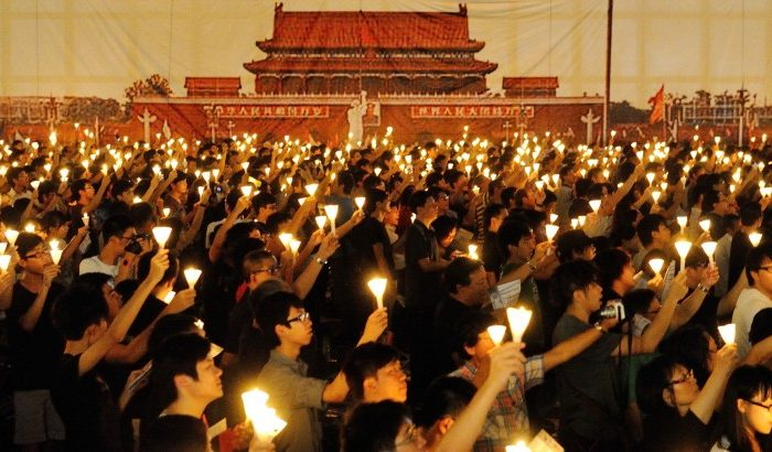 Participants at the 180,000-strong Tiananmen Square Massacre Candlelight Vigil in Hong Kong hold up candles and posters, commemorating the victims. (Sung Pi Lung/The Epoch Times)