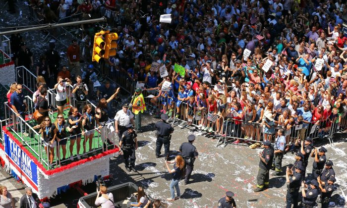 Members of the U.S. women's World Cup championship soccer team ride on a float during a ticker-tape parade honoring the team, as seen from 150 Broadway, in New York, Friday, July 10, 2015. (AP Photo/Adam Hunger)