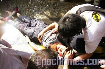 One female journalist lost balance and knocked her head on a rock when she was hit by the water cannon in the head. (Zeng Dongfang/The Epoch Times)