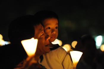 A father and his son participate in the candlelight vigil. (Wen Hanlin/The Epoch Times)