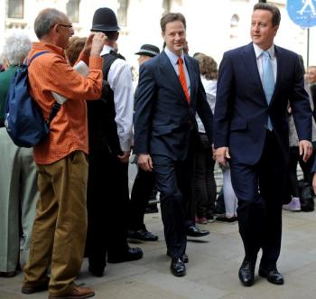 A member of the public (L) takes a photograph of Britain's Conservative Prime Minister, David Cameron (R), and Liberal Democrat Deputy Prime Minister, Nick Clegg (2nd L), as they walk to the Houses of Parliament to attend the State Opening of Parliament.  (Ben Stansall/AFP/Getty Image)