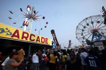 People gather on opening day of the new Luna Park amusement area (L) at Coney Island. (Mario Tama/Getty Images)