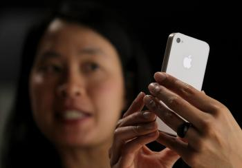 An Apple employee demonstrates the new iPhone 4 at the 2010 Apple World Wide Developers conference June 7, 2010 in San Francisco, California. Apple CEO Steve Jobs kicked off their annual WWDC with the announcement of the new iPhone 4.  (Justin Sullivan/Getty Images)