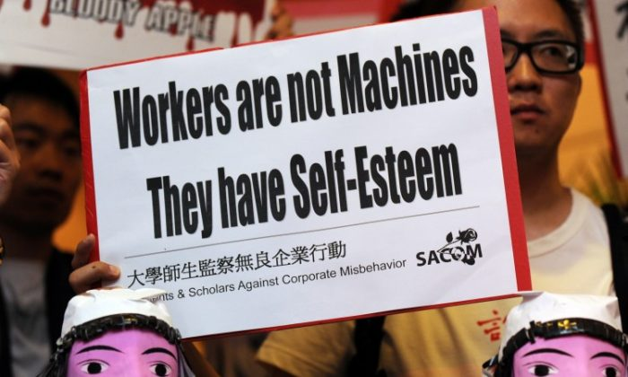 Students protest with model effigies of workers who have committed suicide at Foxconn in China during the company's annual general meeting in Hong Kong on June 8, 2010. The difficult life at the electronics giant has caused despair in its workers. (Mike Clarke/AFP/Getty Images)