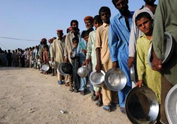 Pakistani flood-affected survivors stand in a queue to get relief food, at a makeshift camp, in Sukkur, on August 23. The near month-long floods have killed 1,500 people and affected up to 20 million nationwide.  (Asif Hassan/GEtty Images)