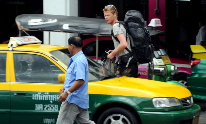 A tourist walks by a Bangkok taxi. A driver, Saksri Ketseekeow, has been promised about $16,000 in rewards, for returning a fortune in gold jewellery to its owner. (Pornchai Kittwongsakul/AFP/Getty Images)