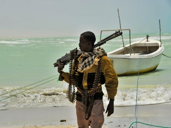 A Somali pirate carries his high-caliber weapon on a beach in the central Somali town of Hobyo on August 20, 2010. (Roberto Schmidt/AFP/Getty Images)