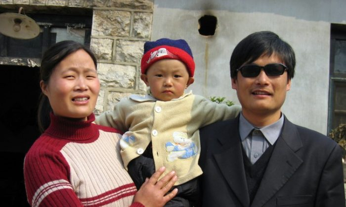 A picture dated March 28, 2005 shows blind activist Chen Guangcheng (R) with his wife and son Chen Kerui outside the home in Dondshigu village, northeast China's Shandong Province. (STR/AFP/Getty Images)