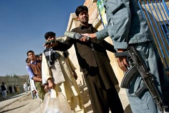 An Afghan policemen security checks voters outside a polling station in Kabul on Sept. 18.  (Manan Vatsayana/AFP/Getty Images)