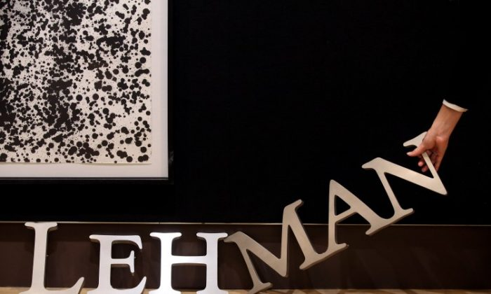 An employee of Christie's auction house manoeuvres a Lehman Brothers corporate logo in 2010. (Oli Scarff/Getty Images)