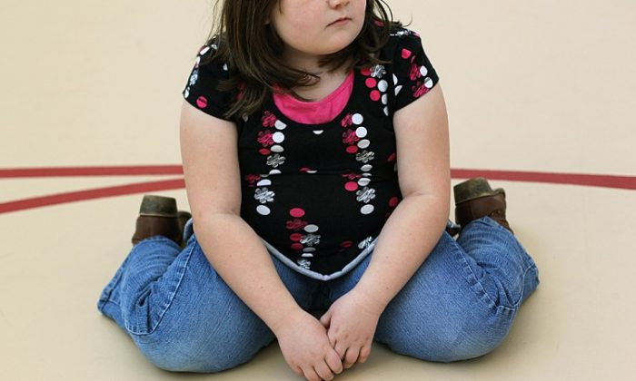 A child sits on the gym floor during a workout. (John Moore/Getty Images)