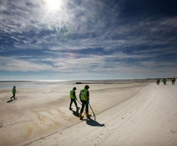Workers clean tarballs from the BP oil spill on Waveland beach December 6, in Mississippi. The National Oil Spill Commission said in a statement Thursday that mismanagement by BP, Transocean, and Halliburton led to the Gulf oil spill.  (Mario Tama/Getty Images)