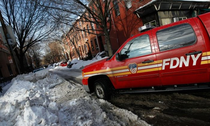 A fire department vehicle stands by as bystanders and emergency workers attempt to free a stuck ambulance on a side street in the Boerum Hill neighborhood of Brooklyn December 29, 2010 in New York City. Many side streets, especially those in the outer boroughs, are still unplowed in the wake of a massive snowstorm that crippled much of New York and left millions of holiday travelers stuck at airports and train stations around the eastern seaboard. (Chris Hondros/Getty Images)