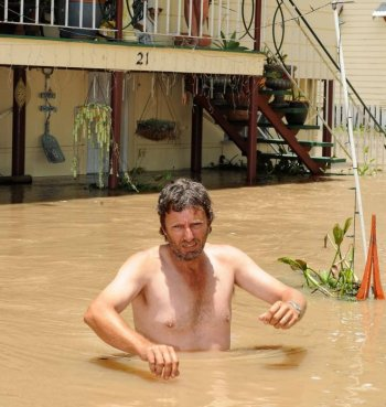 Australia floods: Gary Russell (front) waits for his wife Robyn (top) and dogs to be evacuated by emergency personnel from their flood affected home in Rockhampton on Jan. 6, 2011. (Torsten Blackwood/AFP/Getty Images)