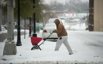 Todd Carnes, an employee of Crosland, spreads salt on the sidewalks surrounding The Catalyst apartments January 10, 2010 in Charlotte, North Carolina.  (Davis Turner/Getty Images)