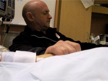 Gabrielle Giffords' husband, Mark Kelly, holds his wife's hand in the congresswoman's hospital room at University Medical Center Jan. 9, 2011 in Tucson, Ariz. (U.S. Rep. Gabrielle Giffords' office via Getty Images)