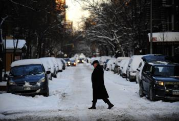 A man crosses a street as fresh snow fell overnight in New York, January 12, 2011.  (Emmanuel Dunad/AFP/Getty Images)