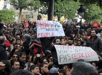 Tunisian demonstrators shout slogans against president Zine El Abidine Ben Ali in front the Interior ministry on the in Habib Bourguiba avenue of Tunis on January 14, 2011. Thousands of protesters demanded the immediate departure of President Zine El Abidine Ben Ali in marches across the country Friday. (Fethi Belaid/Getty Images )