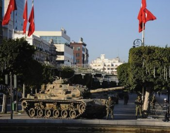 Soldiers stand guard near a tank in Tunis on January 16, 2011. Heavy gunfire was heard in the centre of Tunisian capital on Sunday with security forces exchanging fire with people inside buildings.  (Fred Dufour/Getty Images)