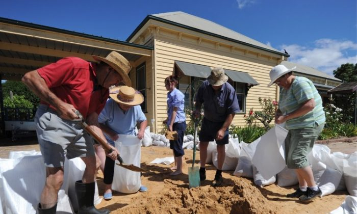 File photo of members of the Dumesny family fill sand bags to protect their home from the rising flood water in the Victorian town of Horsham last summer during heavy rains. (Mark Ralston/AFP/Getty Images)
