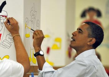 President Barack Obama paints on a wall as he along with First Lady Michelle Obama as their daughters Malia and Sasha take part in a community service project at Stuart Hobson Middle School in celebration of the Martin Luther King, Jr. Day of Service in Washington, DC, on January 17, 2011.  (Jewel Samad/AFP/Getty Images)