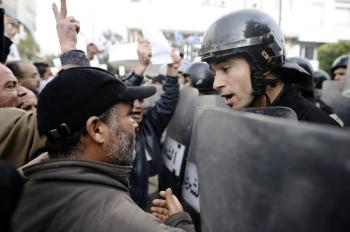 A Tunisian protester talks to a policemen during a demonstration. (Fred Dufour/AFP/Getty Images)