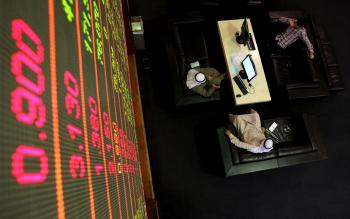 Emirati men sit under a stock market screen at Dubai Financial Market, on January 30, 2011. (Karim Sahib/AFP/Getty Image)